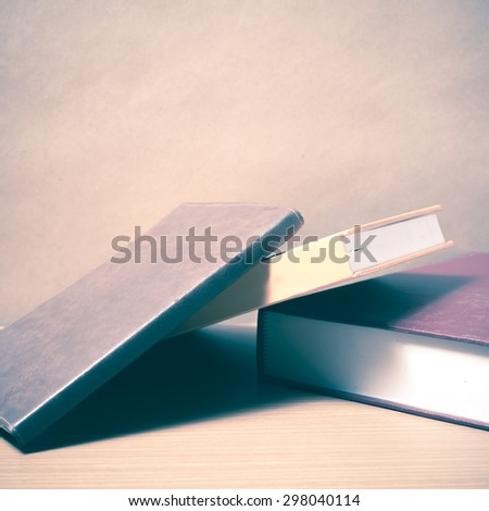 stack of book on wood background vintage style - stock photo