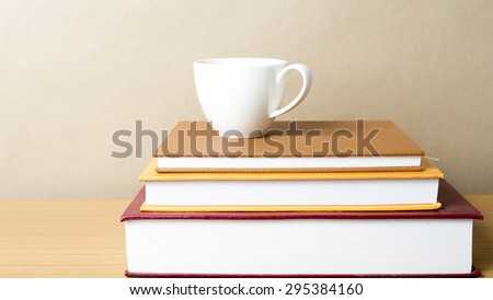 stack of book with coffee cup on wood table background