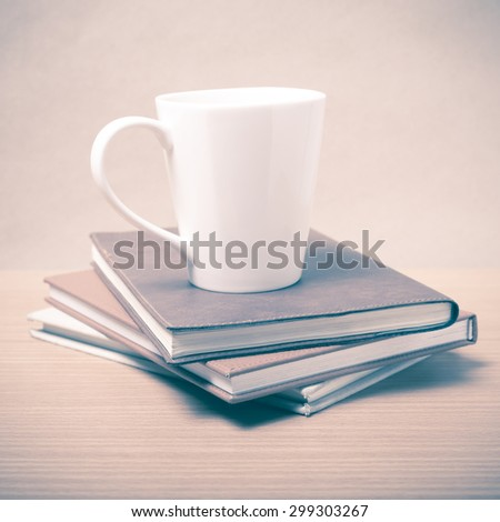 stack of book with coffee mug on wood background vintage style
