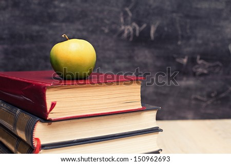 stack of books and a green apple in front of a blackboard