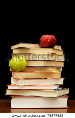 Stack of books and apple On a black background - stock photo