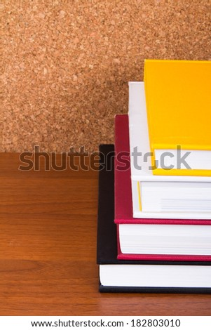Stack of books and cork board on wooden table.
