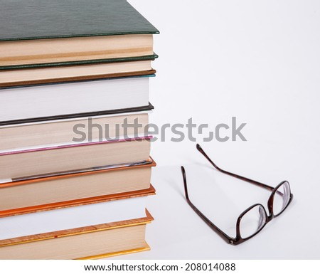 Stack of books and glasses on white background