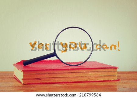 stack of books and magnifying lens, and the phrase yes you can. motivational concept or eduction success concept - stock photo