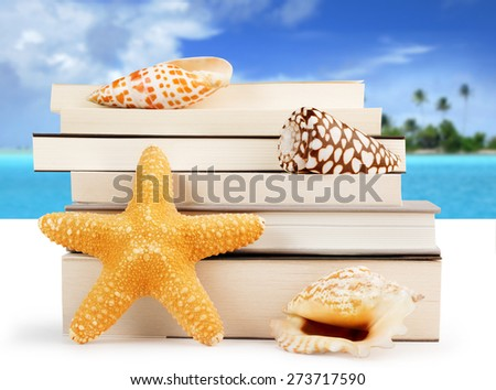 stack of books and seashells on a tropical background - stock photo