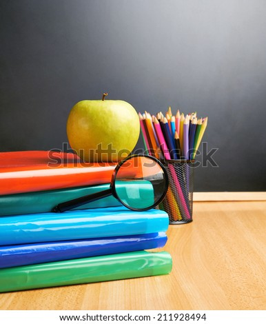 Stack of books, apple, colorful pencils and magnifying glass against the blackboard as a back to school composition