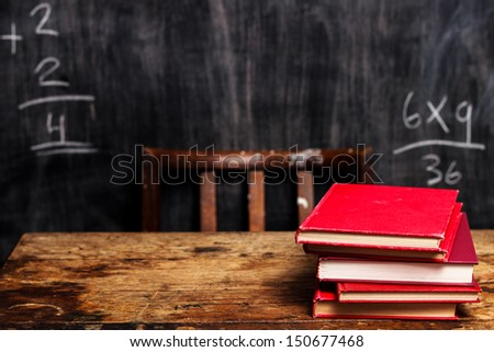 Stack of books by blackboard with bad math - stock photo