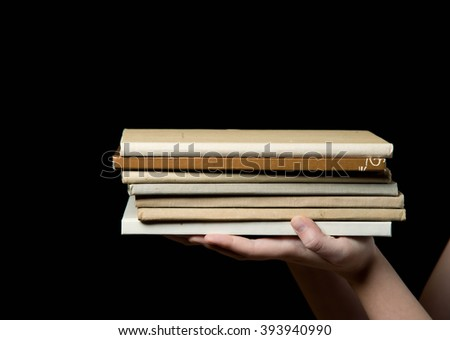 stack of books in a child's hand on a dark background - stock photo
