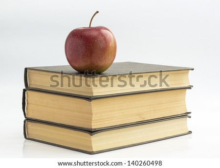 Stack of books in the green cover and red apple