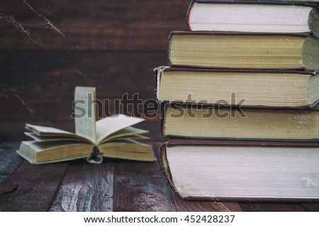 stack of books on a brown wooden table in the background an open book