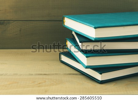 Stack of books on a wooden background - stock photo