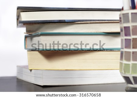 Stack of books on a wooden desk and white background