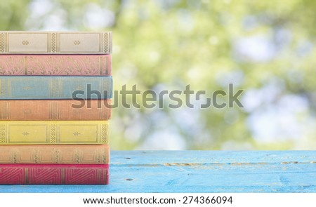 stack of books on blurred nature background - stock photo