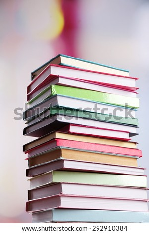 Stack of books on bright background - stock photo