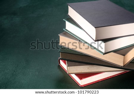 Stack of books on green background