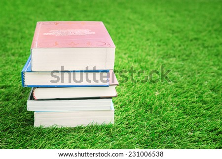 Stack of books on green grass - stock photo