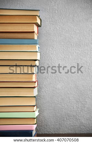 Stack of books on grey wall background