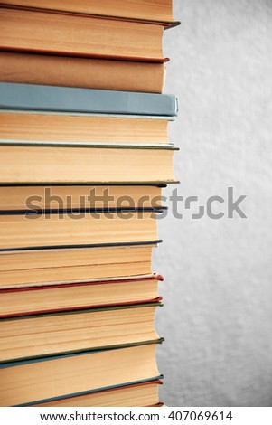 Stack of books on grey wall background, close up