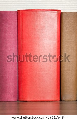 stack of books on the shelf, blank spines, close-up - stock photo