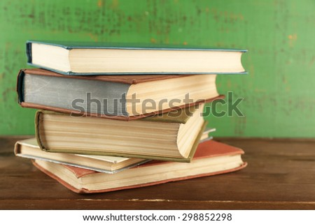 Stack of books on wooden background - stock photo