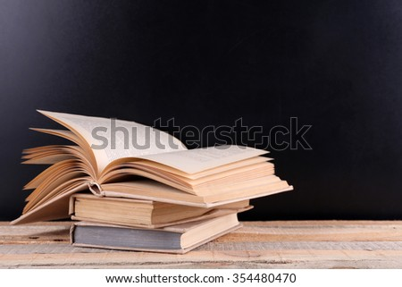 Stack of books on wooden table,  black background - stock photo