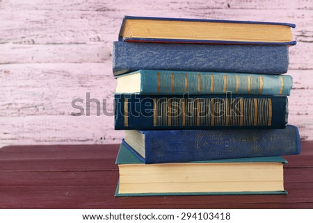 Stack of books on wooden table on pink wooden wall background - stock photo