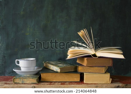 stack of books, open book, cup of coffee, chalk board, free copy space - stock photo