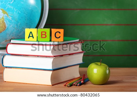 Stack of books, red apple, globe and pencils - stock photo