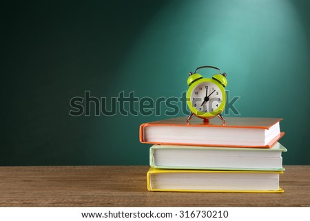 Stack of books with alarm clock on desk on green chalkboard background - stock photo