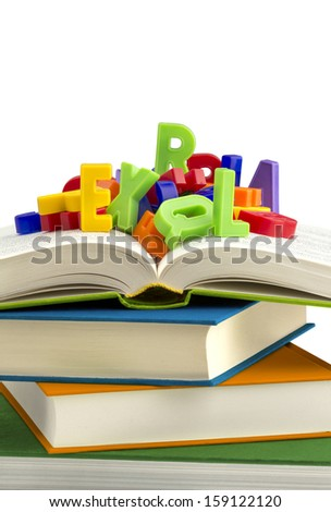 stack of books with colorful plastic letters on top - stock photo