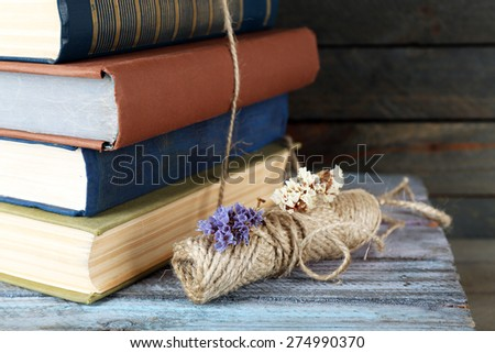 Stack of books with dry flowers on table close up - stock photo