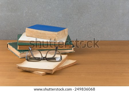 stack of books with glasses - stock photo