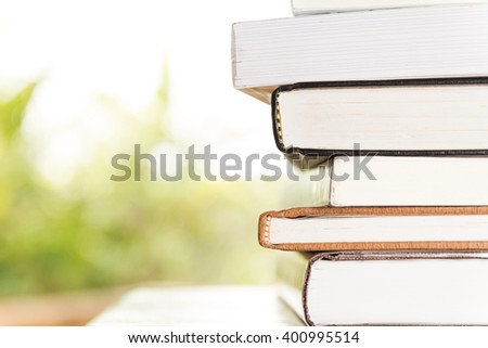 stack of books with green bokeh background - stock photo