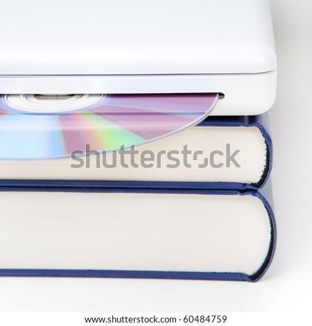 stack of books with laptop computer and CD - stock photo