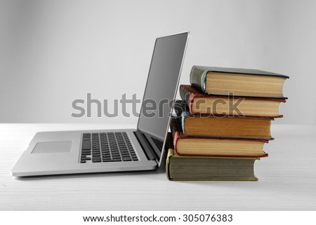 Stack of books with laptop on gray background