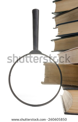 Stack of books with magnifying glass isolated on white background. Search information. - stock photo