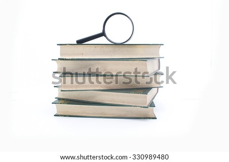Stack of books with magnifying glass. Search information.