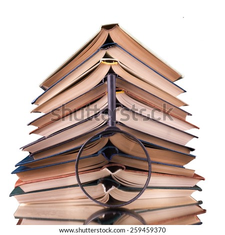 Stack of books with magnifying glass. Search information. Copy space for text. - stock photo