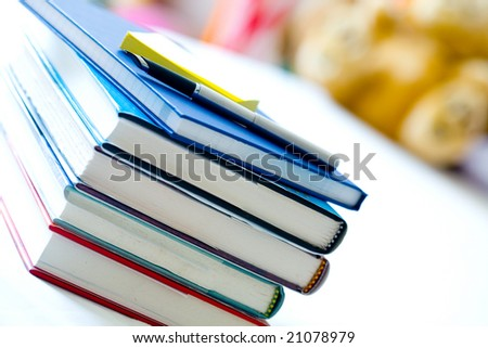 Stack of books with notepad and pen in little girl's room