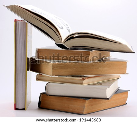 stack of books with open book and the stand of books isolated on white background - stock photo