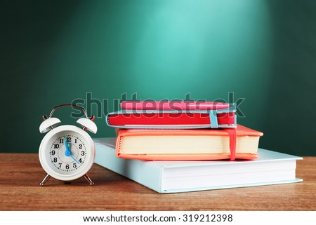 Stack of books with pen and alarm clock on desk on green chalkboard background - stock photo