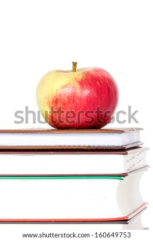 Stack of books with red apple on top over white background