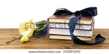 Stack of books with ribbon and flowers isolated on white - stock photo