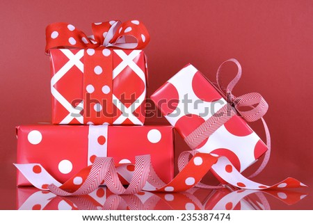 Stack of bright red and white polka dot and check festive Christmas or Valentine gift boxes on red background. - stock photo