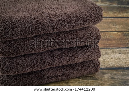 Stack of brown, organic cotton towels on a dark wooden background.  - stock photo