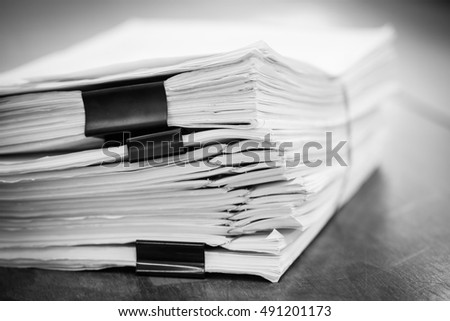 Stack of business report paper files with black clips in black-w