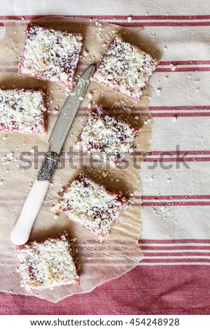 Stack of cake or cookies with plum, strawberry, raspberry and cherry jam or marmalade with sweet crumbs, cinnamon and nuts on a parchment paper, selective focus - stock photo