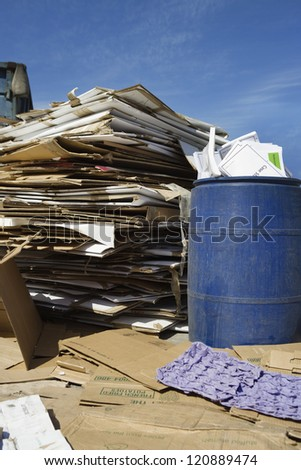 Stack of card boxes with waste bin in junkyard - stock photo