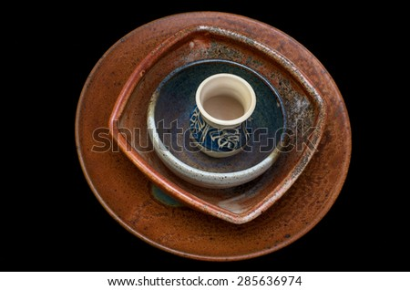 stack of ceramic bowls and small pitcher isolated against black - stock photo