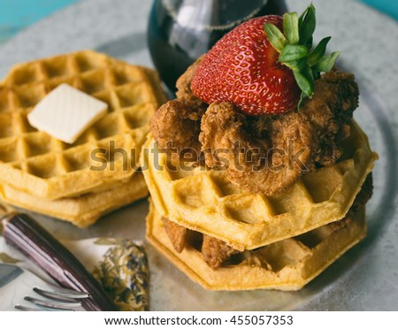 Stack of chicken and waffles on a galvanized steel plate. Garnished with a strawberry.  Maple syrup on the side.